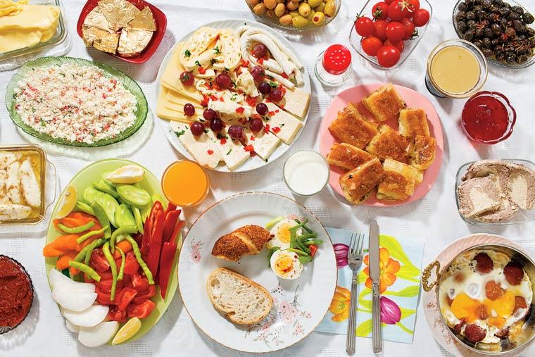 Miel et crème épaisse sur du pain grillé (kaymak), olives vertes et noires, oeufs frits et saucisse, oeufs durs, sirop épais de raisin (pekmez), assortiment fromages au lait de vaches, de brebis et de chèvres, confitures de mûres et de coing, pâtisseries, pain, tomates, concombres, radis blancs, pâte de poivrons rouges grillés; noisettes, lait et jus d'orange