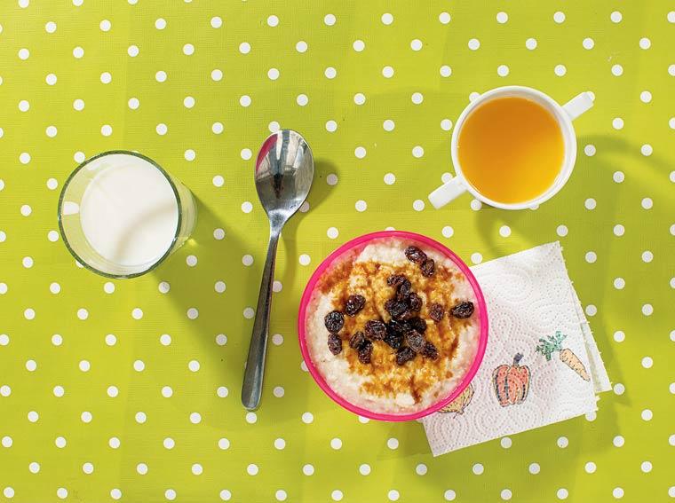 Porridge avec raisins sec et sirop d'érable, verre de lait et jus d'orange frais