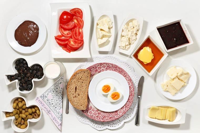 Pain complet, olives vertes et noires, Nutella, tranches de tomate, œuf dur, confiture de fraise, beurre trempés dans le miel, assortiment de fromages turcs