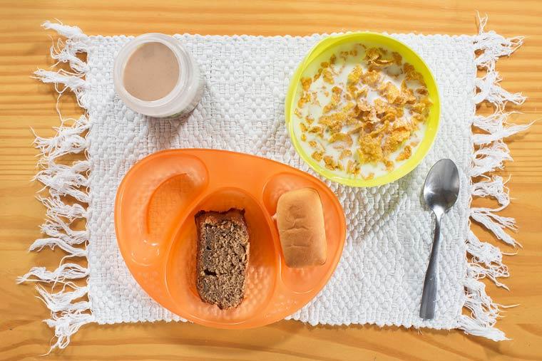 Chocolat au lait, céréales, gâteau à la banane, pain doux (bisnaguinha)
