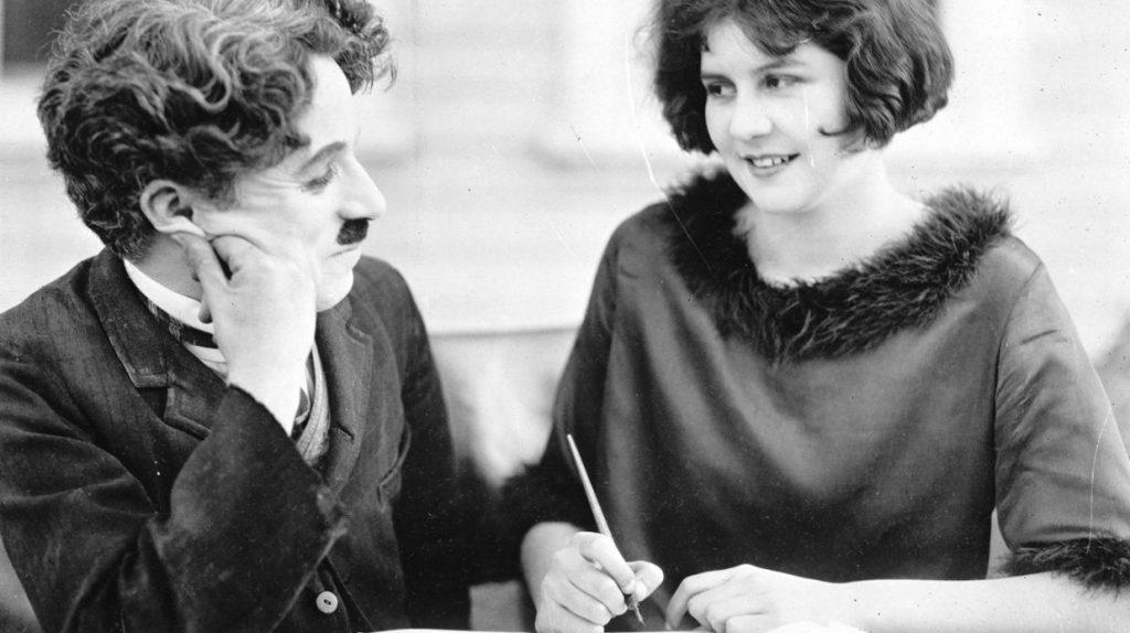 Charlie Chaplin écriture poème interview noir et blanc moustache sourire femme brune regard cheveux bouclés pose