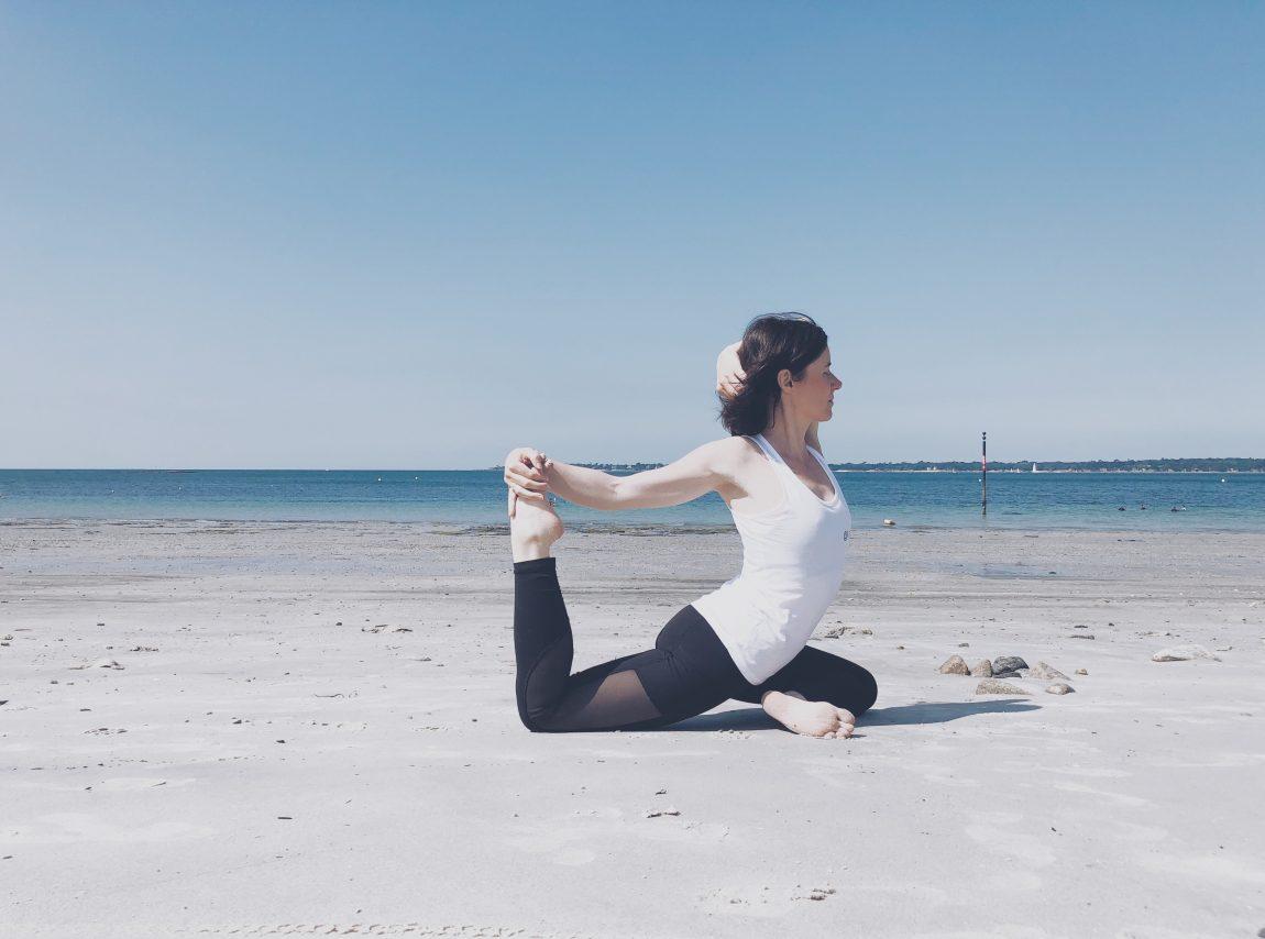yogi girl femme yoga pose yoga plage mer océan bleu ciel sable legging yoga noir débardeur blanc yoga get yogi