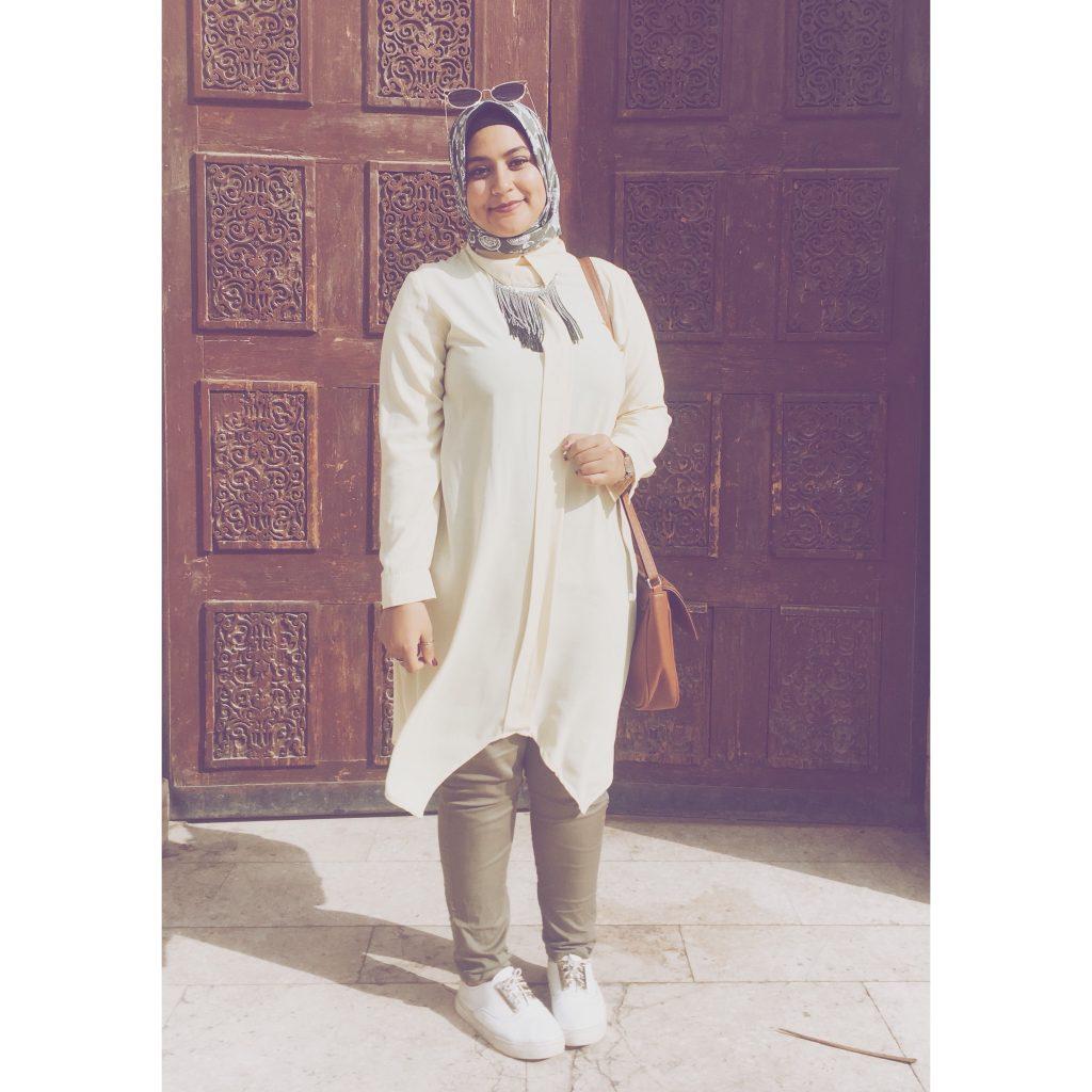 femme voile voilée porte architecture orientale moucharabieh baskets blanches sac marron sourire tunique beige pantalon kaki porte marron lunettes de soleil femme egyptienne