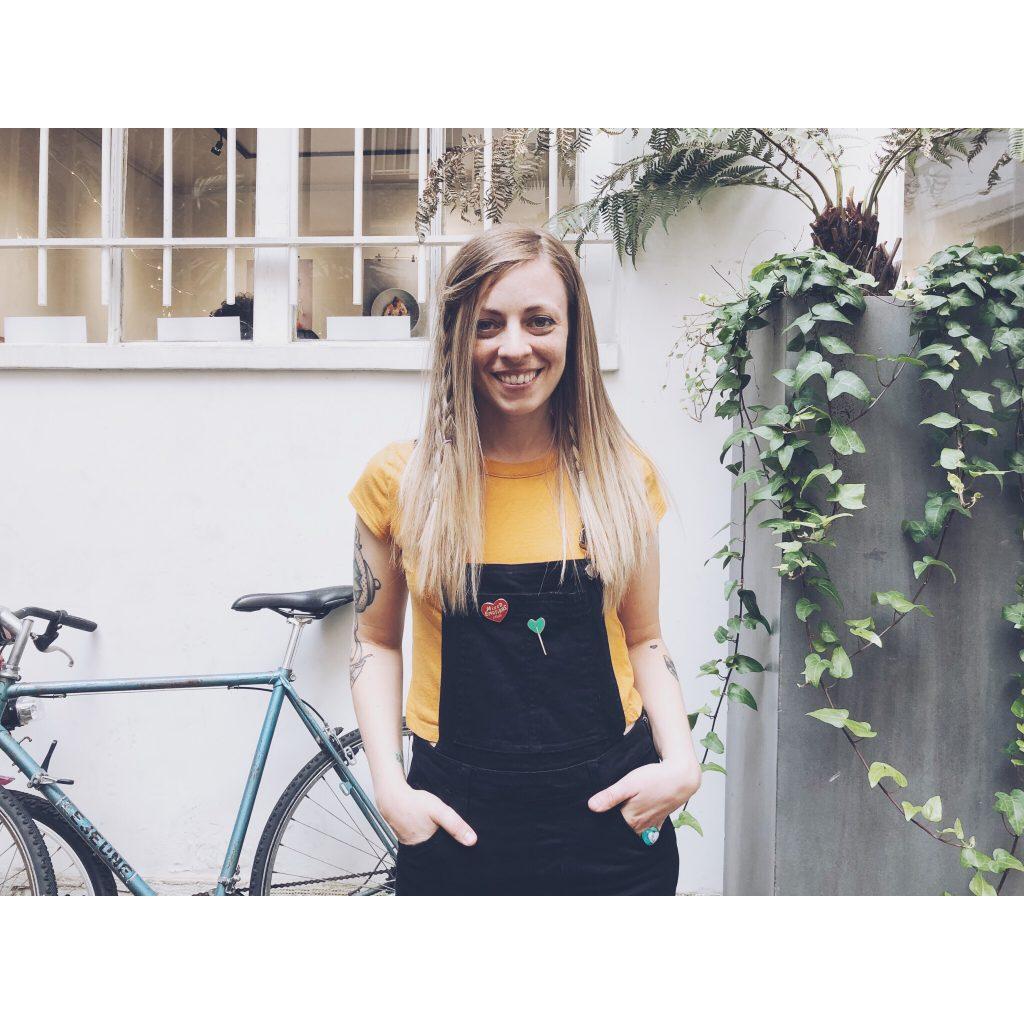 femme blonde cheveux brushing salopette noire t-shirt jaune pins vélo libre mur blanc fenêtre plantes cheveux longs sourire yeux bleus tatouages