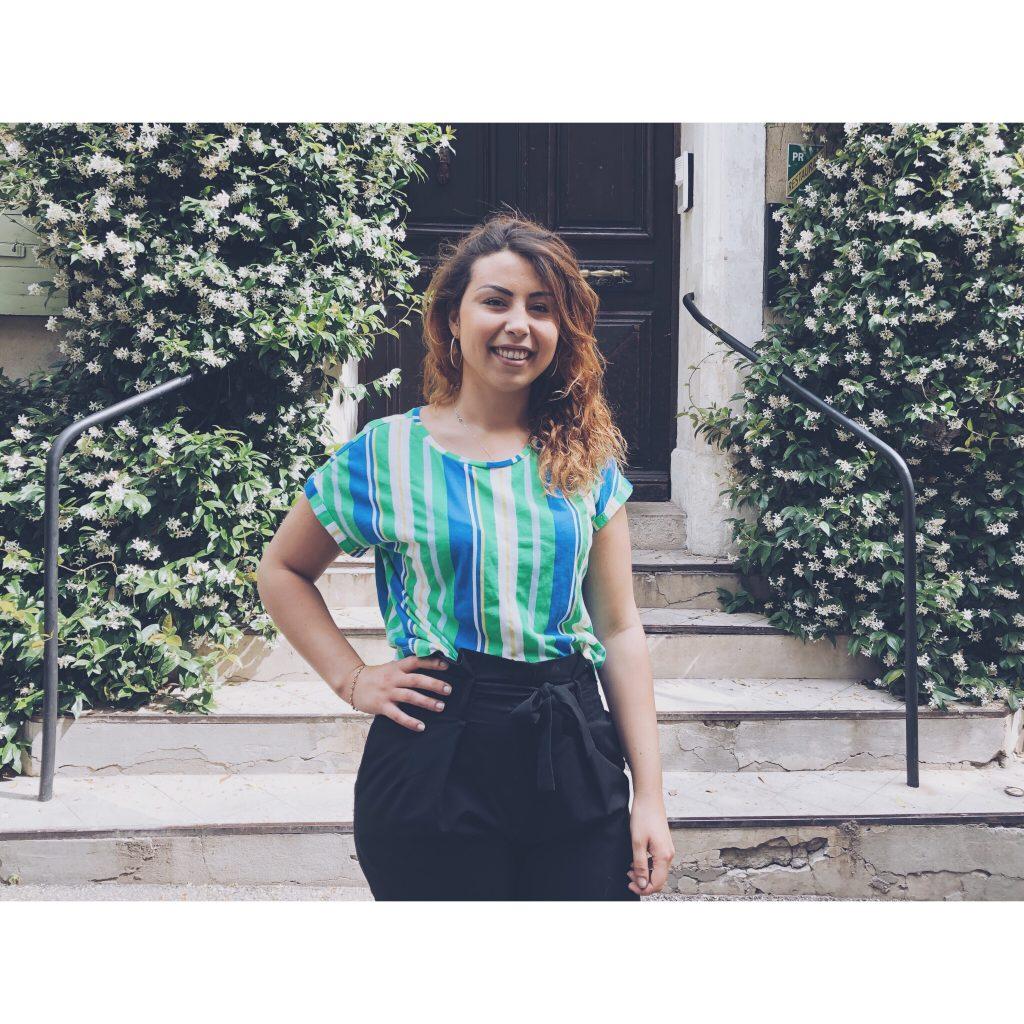 t-shirt vert rayures blanc jasmin fleurs verdure nature entrée porte cheveux sourire femme fille pantalon noir cheveux colores main sur la hanche