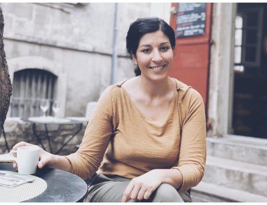 t-shirt marron top taupe chignon coiffure cheveux bruns femme brune sourire dents blanches cafe terrasse pantalon kaki rue porte rouge escaliers